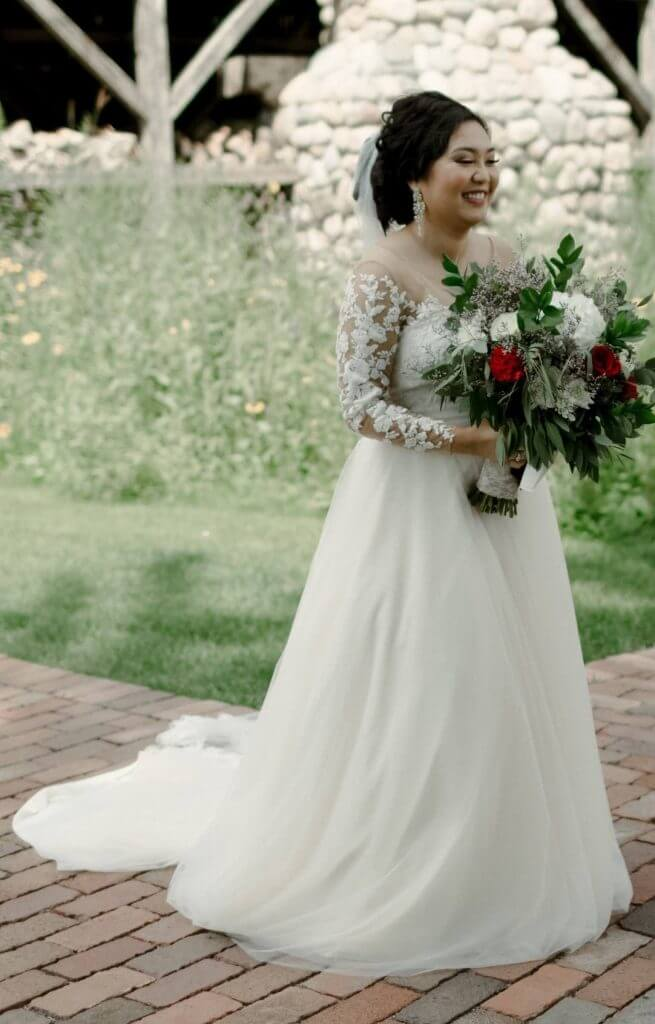 Anomalie creates online custom wedding dresses, including gowns with a-line silhouette, lace, full length sleeves, and skin tone illusion mesh.