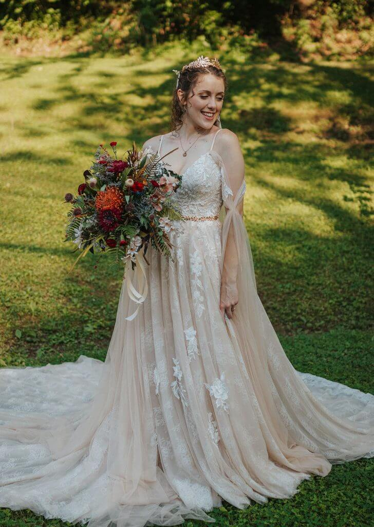 Anomalie creates online custom wedding dresses, including gowns with a-line silhouette, lace, spaghetti strap sleeves, cape and romantic layers.