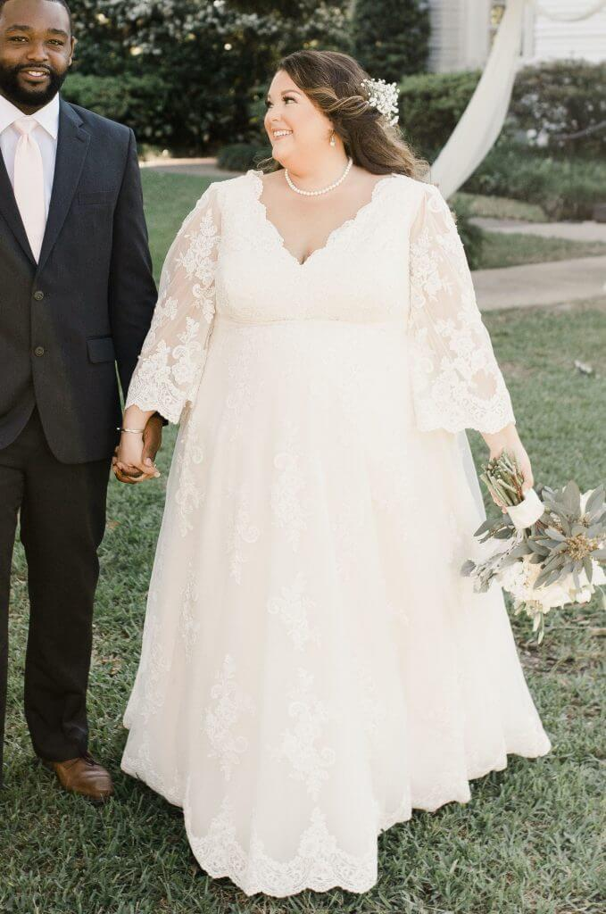 Anomalie creates online custom wedding dresses, including gowns with a-line silhouette, lace, bell sleeves, and scalloped hem.