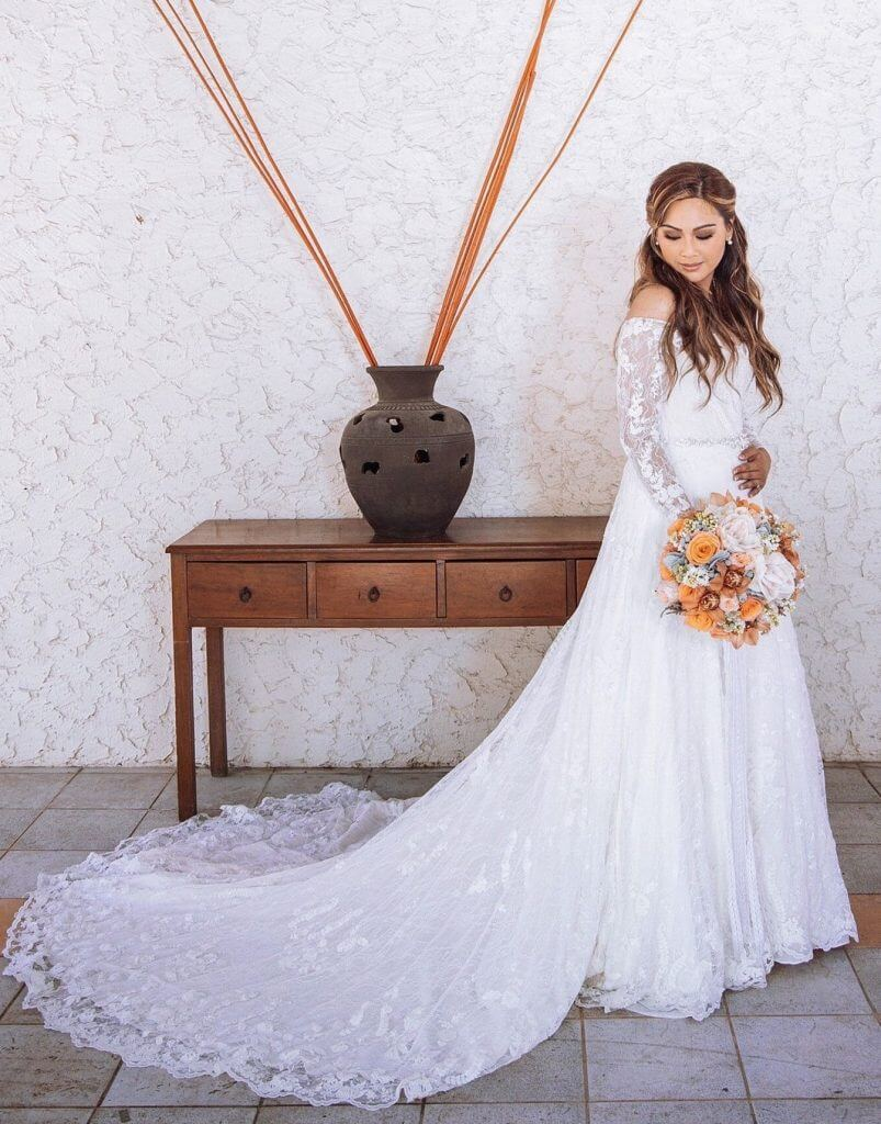 Anomalie creates online custom wedding dresses, including gowns with a-line silhouette, multiple laces, long sleeves, and scalloped hem.