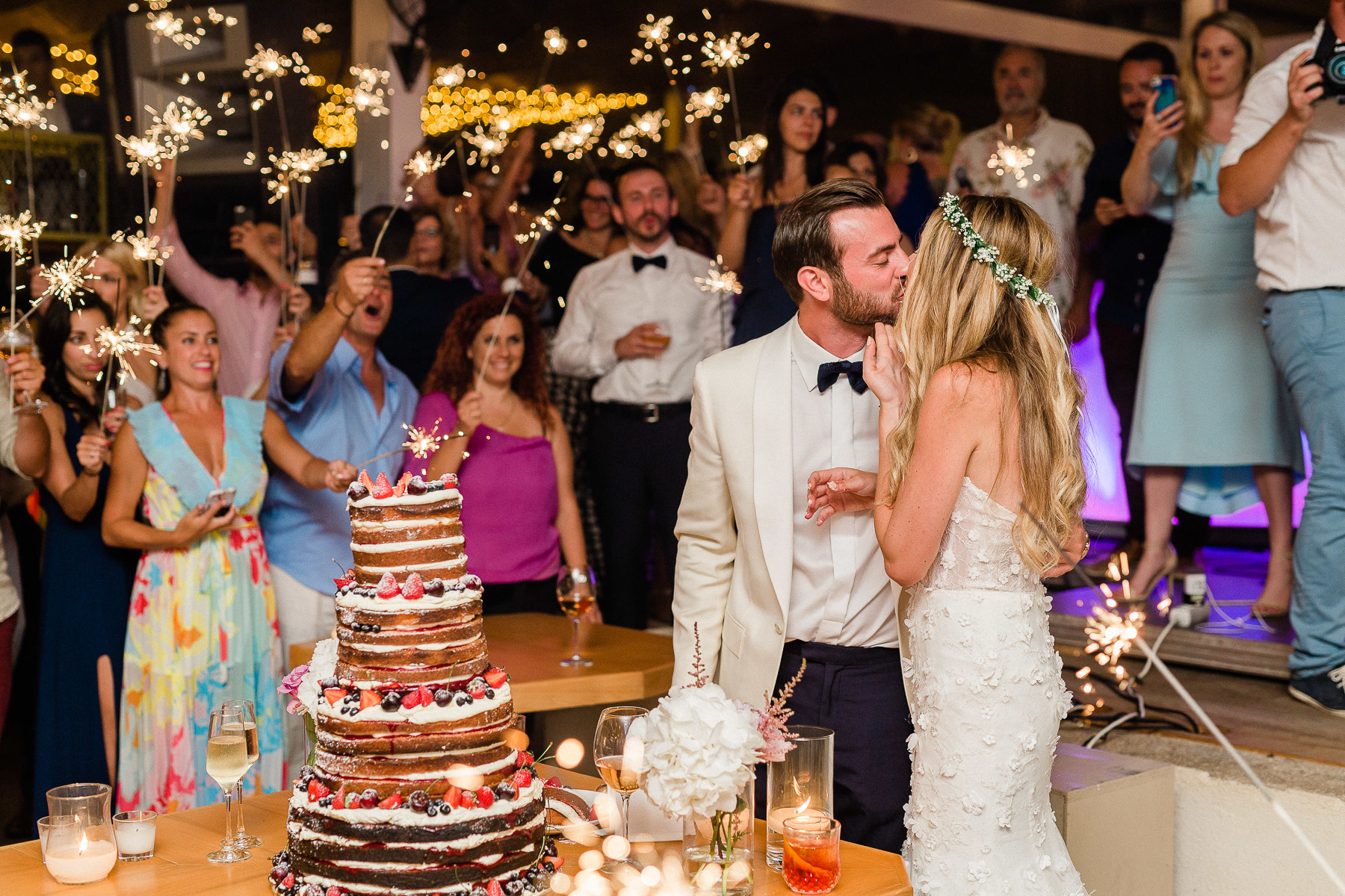Cake-cutting: bride and groom kiss.