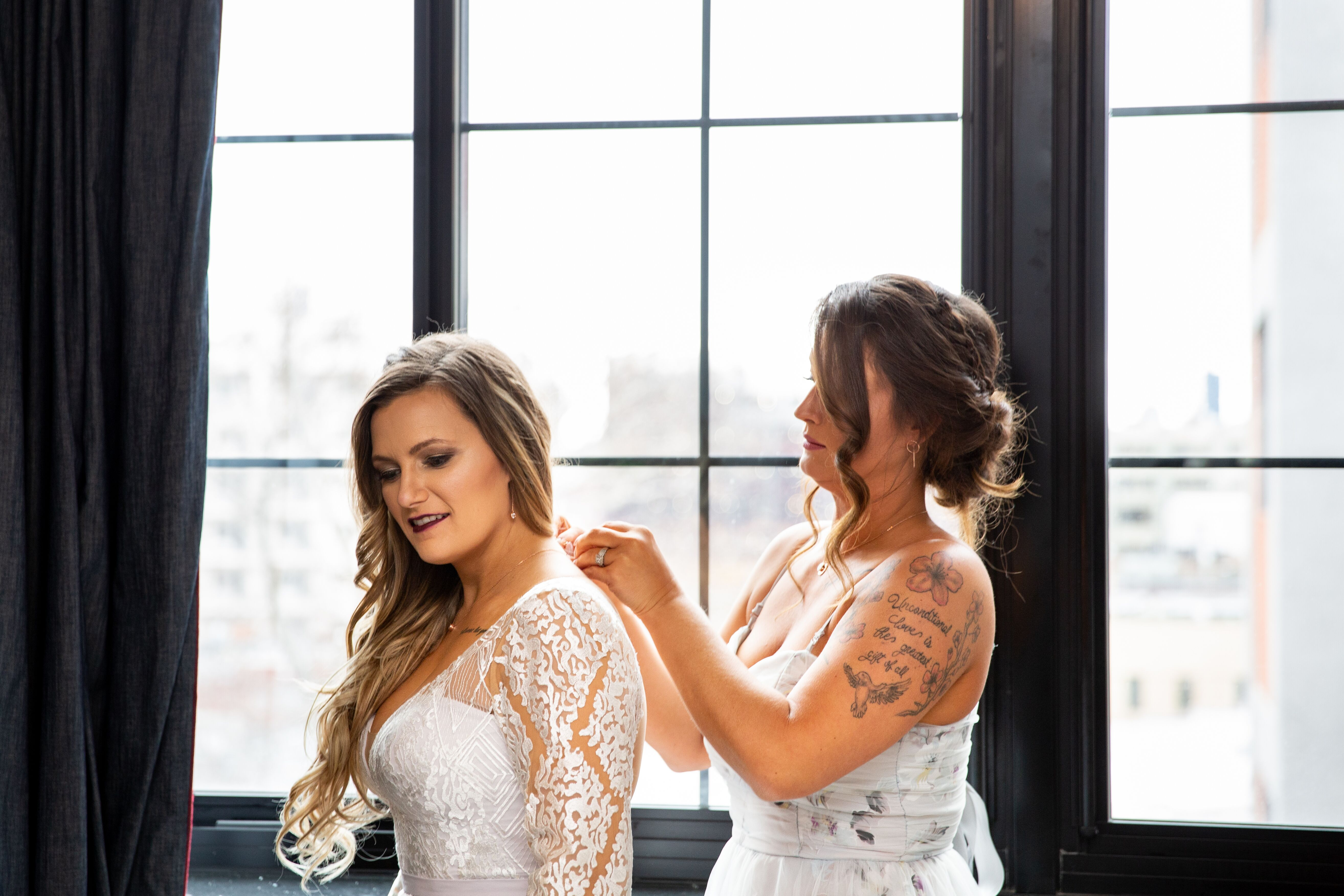 Anomalie bride getting ready in custom wedding dress with boho style and lace sleeves
