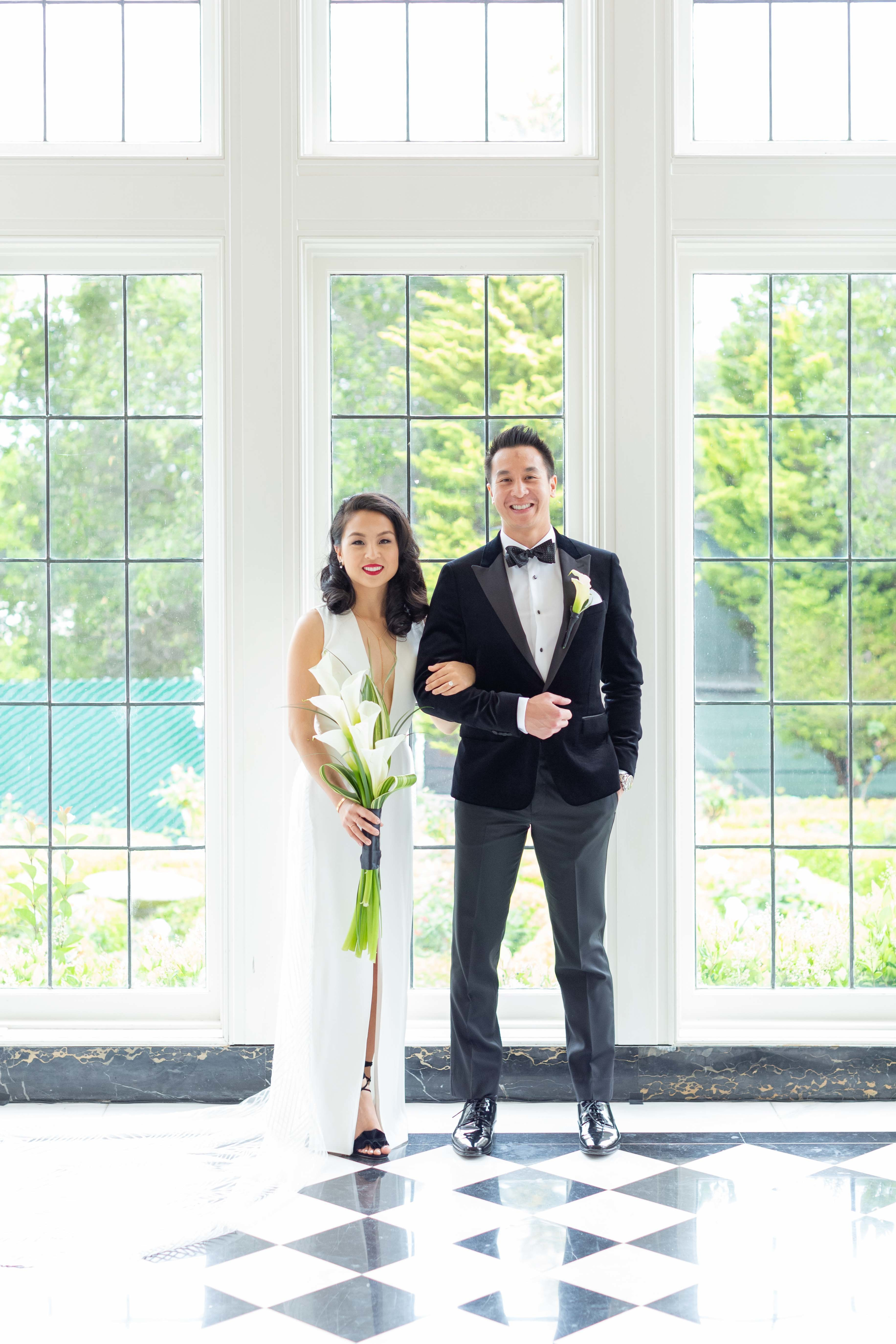 Bride and groom. Bride wears a sleek column dress with a plunging neckline.