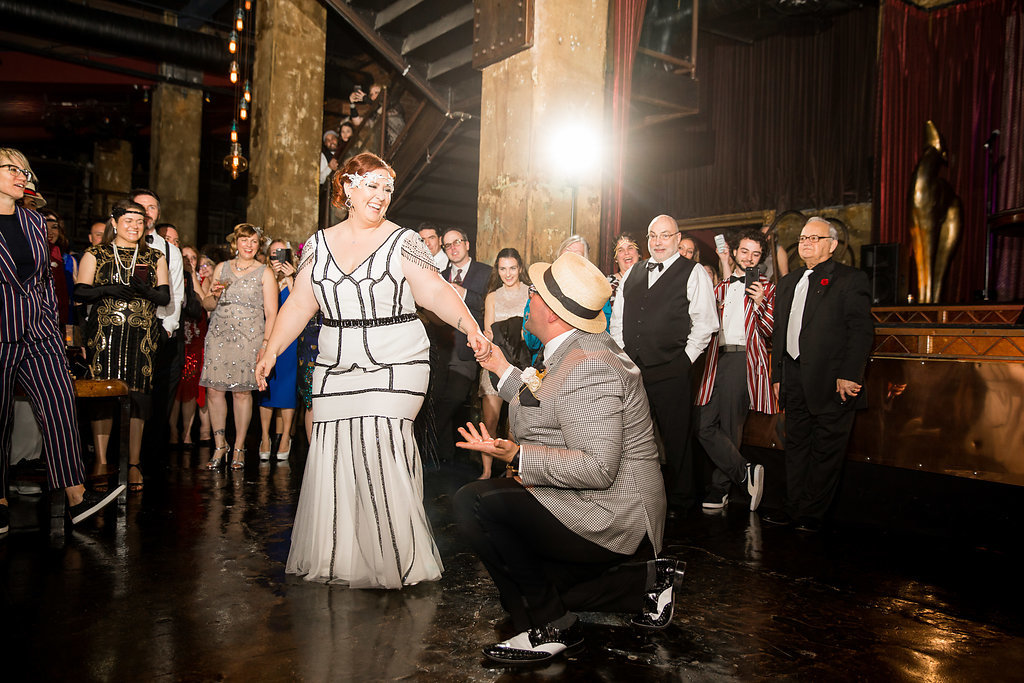 A Gatsby-inspired wedding: retro-looking guests looking at the bride in her glam gown, while her dapper groom kneels on one knee and grabs her hand.