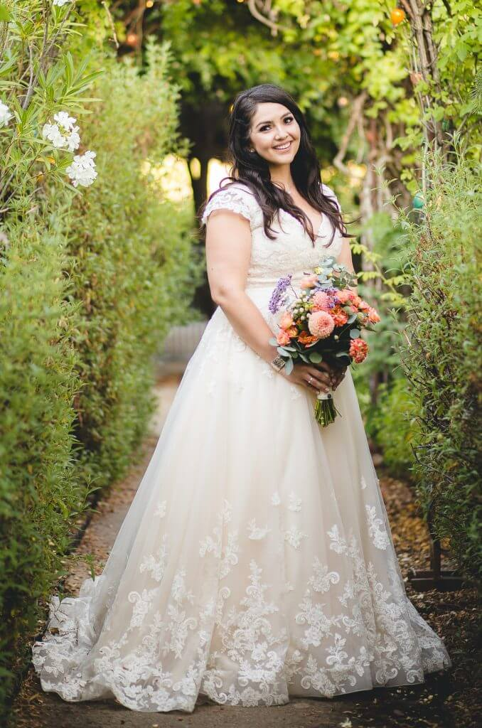 Anomalie creates online custom wedding dresses, including gowns with a-line silhouette, floral lace, cap sleeves.