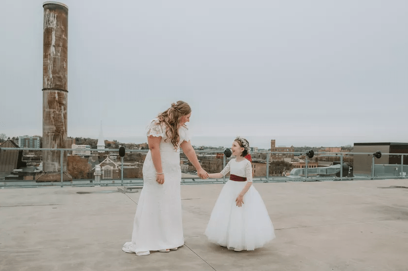 Bride and flower girl holding hands on a rooftop.