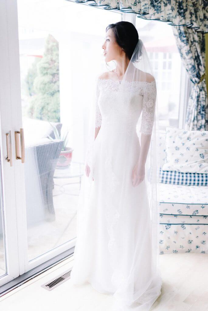 Anomalie creates online custom wedding dresses, including boho gowns with soft white poly organza and simple sheet lace and off-the-shoulder sleeves.
