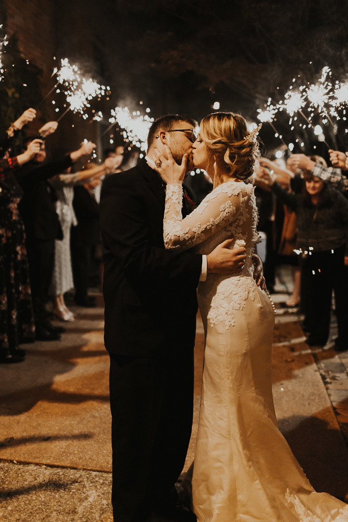 Bride wearing lace sheath dress, kissing the groom amidst sparklers.