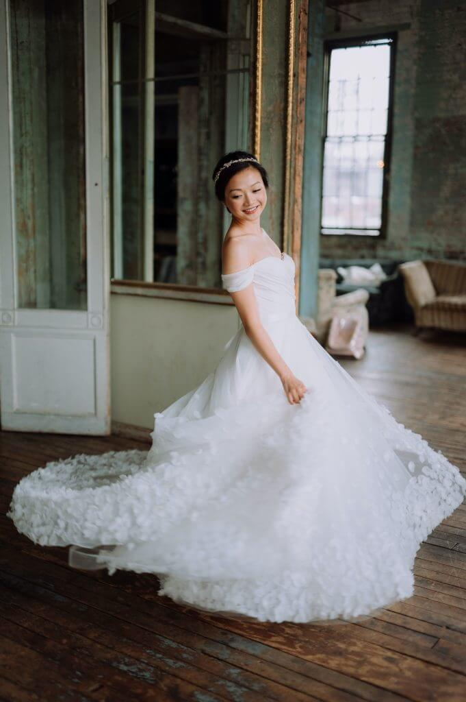 Anomalie creates online custom wedding dresses, including regal, off-the-shoulder, lace, a-line gowns.