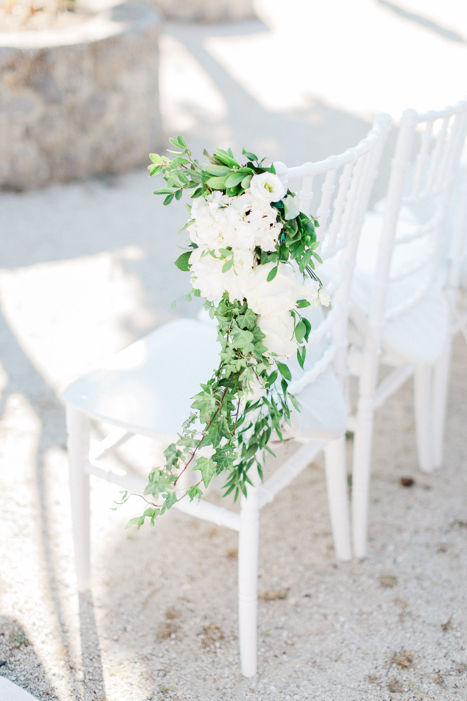 White chairs with white flower arrangements.