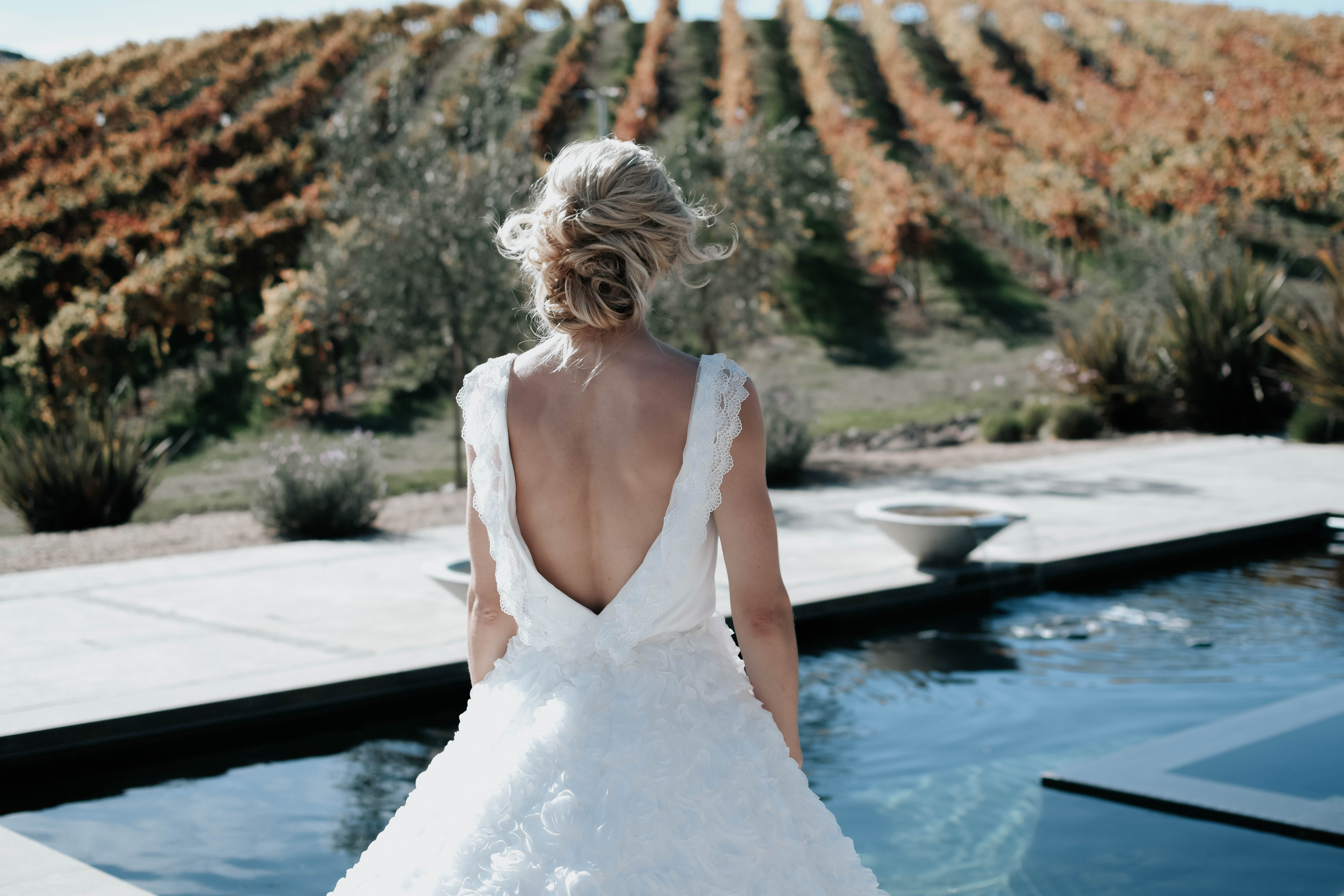 Bride from her back. She's facing a backdrop of vines and fountains.