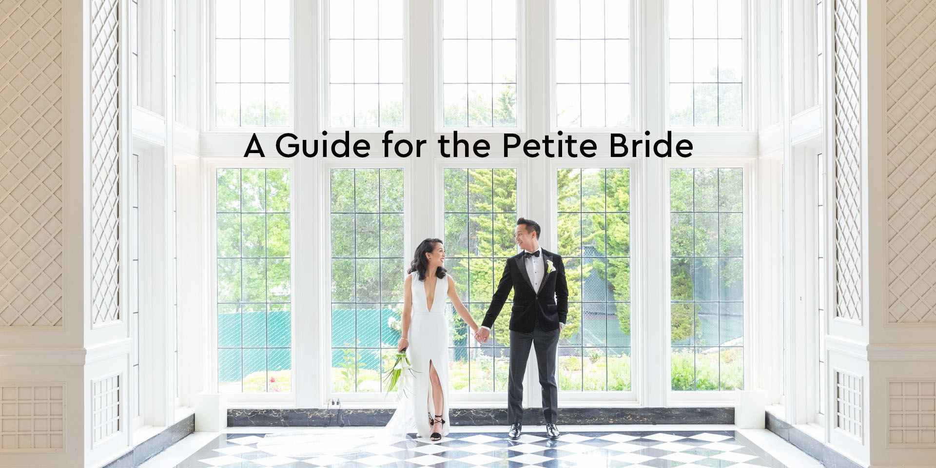 Bride and groom holding hands in big bright room. Bride wears a sleek column gown with a plunging neckline.