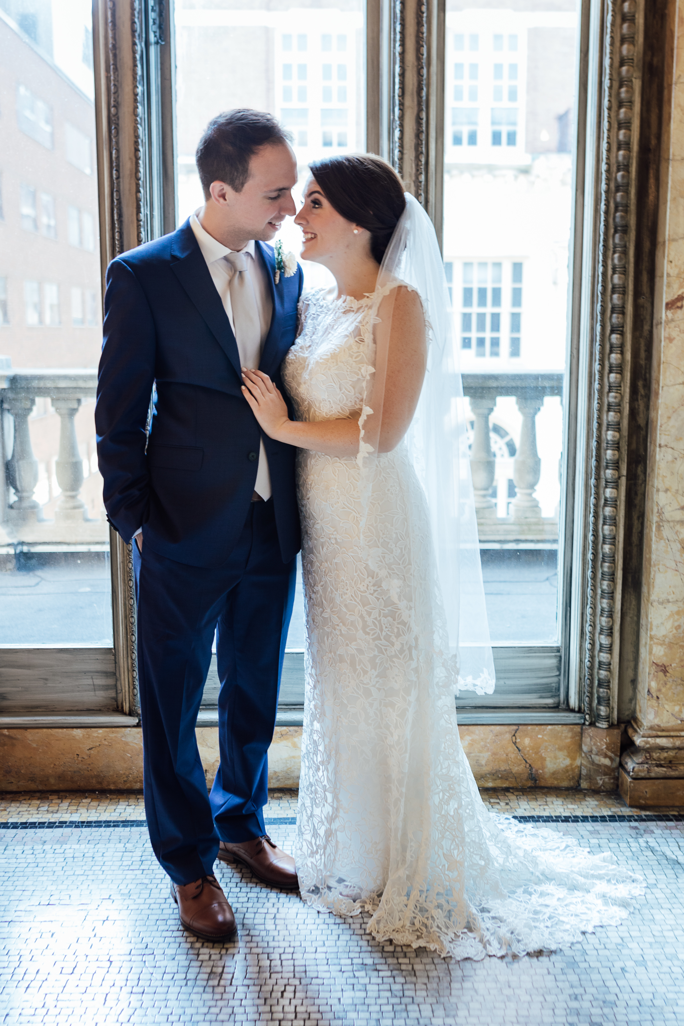 Bride and groom. Bride wears lace sheath dress and a tulle, lace-trimmed veil.