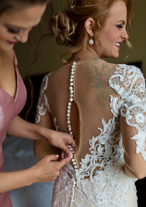 Bride getting her dress buttoned-up in the back. The illusion material showcases her tattoo.