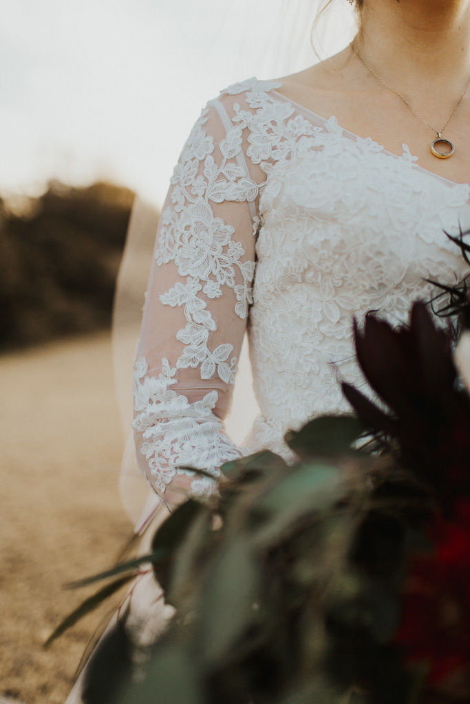 Close-up of Anomalie bride wearing sheer long sleeves with lace appliqués.