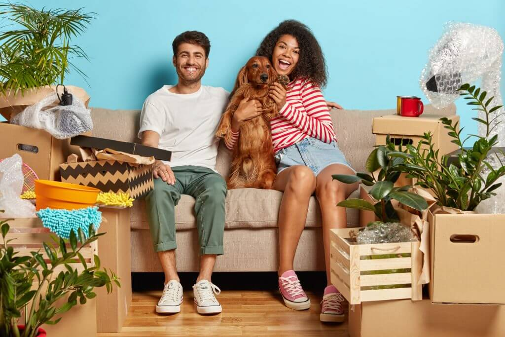 Young couple with their dog sitting on their couch.
