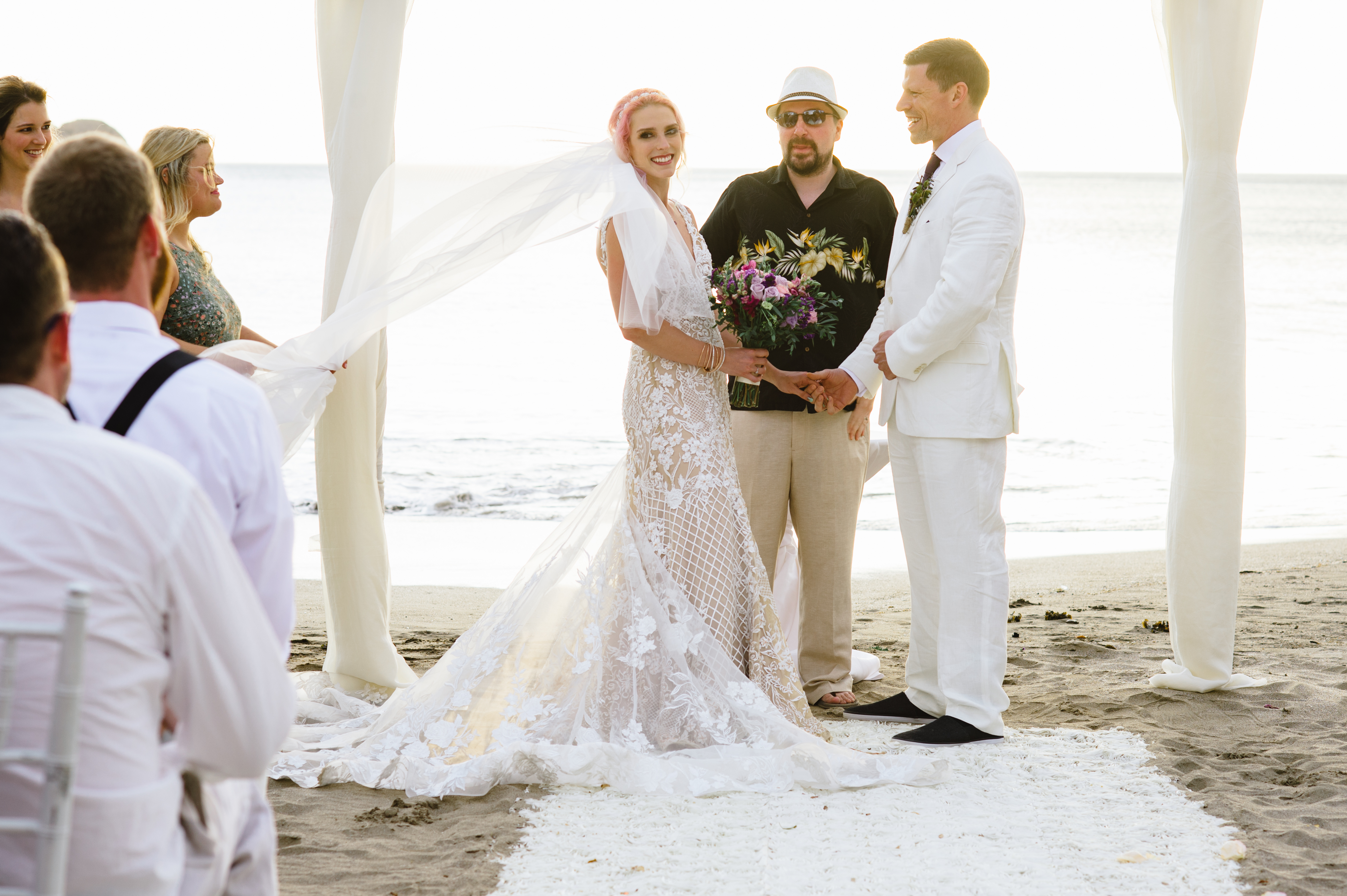 Sunset vows in Costa Rica with bride wearing anAnomalie wedding dress