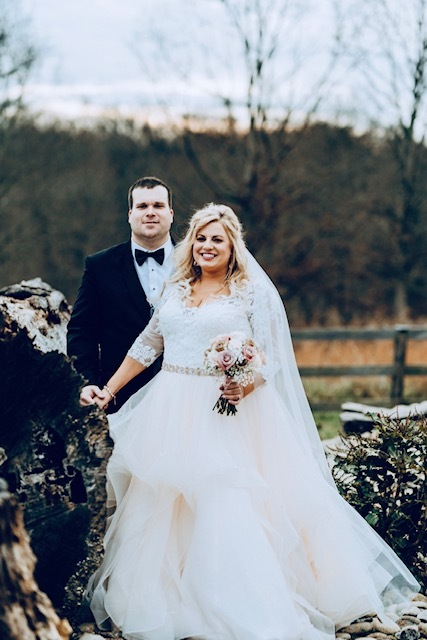 Anomalie bride wearing a voluminous tiered skirt, holding hands with her groom.