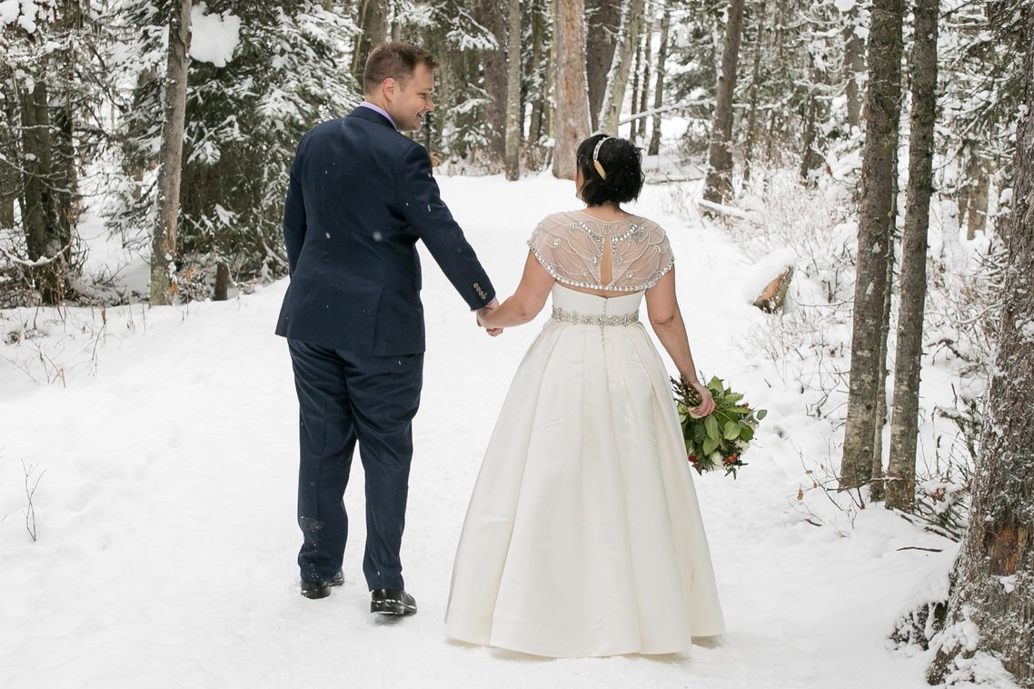 Bride and groom standing in the snow. Bride wears a shimmery topper that covers her tattoo.